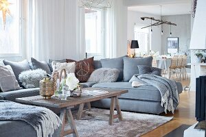 U-shaped grey sofa and rustic coffee table on trestles in open-plan living area