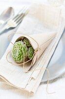 Tüte aus Packpapier und Schnur mit Sempervivum auf einem Teller