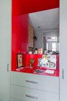 Fitted cabinets painted pale grey with mirror on back wall of red niche