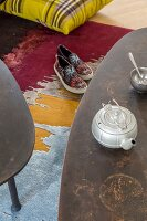 Vintage teapot on coffee table above slip-on sneakers on colourful rug