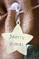 Star-shaped gift tag reading 'Merry X-mas' on hessian bag