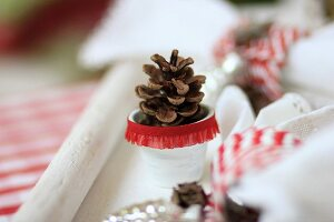 Pine cones in tiny white plant pots decorated with red ruffled trim