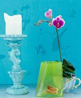 Pale blue candlestick, green glass vase and orchid in vintage-style coffee cup