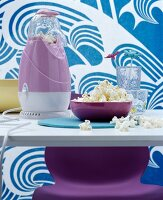 Iconic purple popcorn machine on dining table in front of fabric with blue and white pattern of waves