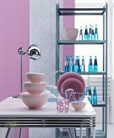 Iconic stainless steel shelves, chrome dining table and pink, fifties-style kitchen accessories