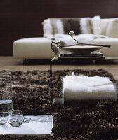 Wohnzimmer in Weiss-Braun mit modernem Recamiere und Beistelltisch auf Hochflorteppich