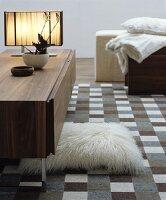 Wohnraum in Naturtönen mit Sideboard und kariertem Teppich