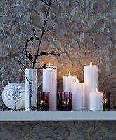 Stimmungsvolle winterliche Dekoration aus Vasen, Windlichtern und Stumpenkerzen auf weissem Wandregal