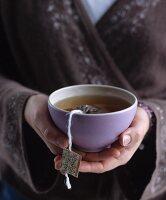 Frau im Kimono hält Teeschale in den Händen