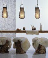 Baumstämme mit Schaffellen als Sitzgelegenheiten an rustikalem Holztisch mit dekorativen Bambus-Hängeleuchten