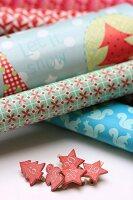 Verschiedene Geschenkpapierrollen und beklebte Wäscheklammern mit Zahlen für Adventskalender