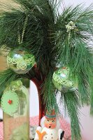 Glass baubles decorated with green trim hung from pine branch
