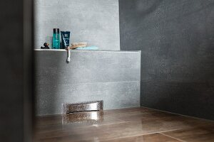 Detail of a floor-level, grey-tiled shower with bathing utensils on a narrow shelf
