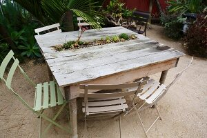 Miniature bed of succulents integrated into rustic wooden table outdoors