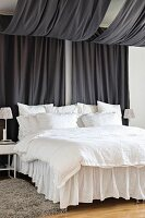 Bed with white bed linen and valance under canopy made from two lengths of black fabric