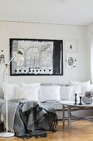 White, vintage-style cushions on grey sofa below black and white artwork