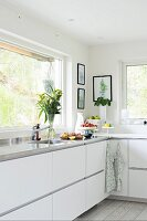 Modern kitchen with white fronts and stainless steel worksurface