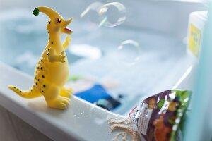 A bath toy dino on the edge of a bathtub