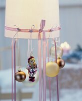 Lampshade festively decorated with ribbons and Christmas tree baubles