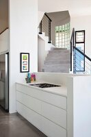 Kitchen counter with white base unit against half-height wall; concrete staircase with black balustrade in background