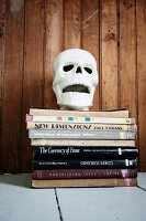 Skull ornament on stacked books against board wall