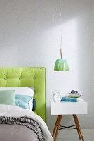 A modern bedside table next to a bed with a lime green padded headboard against a wall with a light-coloured liberty pattern