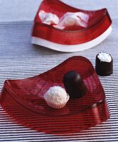 Sweets in two curved, red bowls on black and white striped surface
