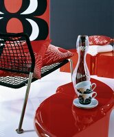 Retro-style arrangement of black chair with cord seat, cups on red side table and red, white and black picture on wall