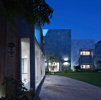 Tall, illuminated stone façade with terrace doors, garden, stone-paved area in front of concrete arcade at twilight