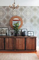 Framed photos on solid-wood sideboard below round mirror on wall with op-art wallpaper