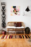 Patterned rug on wooden floor in front of cane couch with cushions next to ethnic sculpture hung on wall