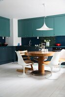 Kitchen with two-tone cabinets, round dining table and designer chairs