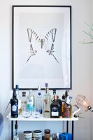Drinks trolley below framed picture of butterfly