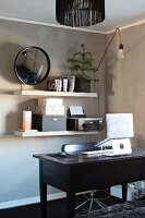 Notebook on stand on dark wooden desk in front of office utensils on white shelves mounted on pale brown wall