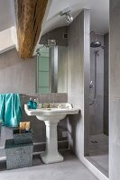 Bathroom with shower area, vintage-style pedestal sink and rustic roof beam in renovated attic