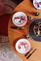 Runder gedeckter Holztisch, mit folkloristischen Kreuzen und Namensschildern