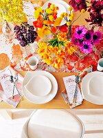 Gedeckter Tisch mit üppiger Blumendeko in Gelb- und Rottönen, Menükarten und gesprenkeltem Tischläufer