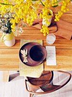 Blick auf gedeckten Tisch mit Holzbrettchen, Menükarte und gelben Blumen