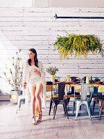 Junge Frau lehnt an gedecktem Tisch mit Industrie-Stühlen und üppigem hängendem Blumenschmuck