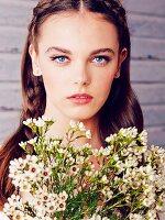 Junge Frau mit geflochtenem Haar und Blumenstrauß