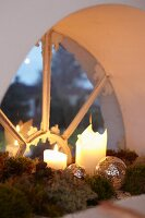 Old semicircular window decorated with moss, candles and baubles