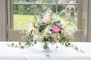 Romantisches Blumenbouquet auf einer Hochzeitstafel