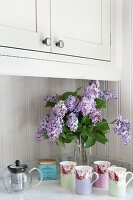 Vintage-style beakers and vase of lilac on kitchen counter with Carrara marble worksurface