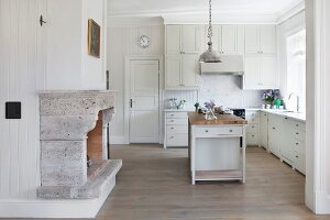 Spacious, white, country-house kitchen with free-standing island counter below metal pendant lamp and open fireplace with stone surround