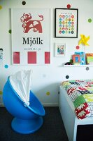 Child's blue pod chair and bed with colourful bedspread below posters on polka-dot wall