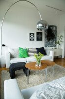 Sofas and round side tables on long-pile rug and classic, 60s' Italian lamp in living room