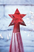 A red star tree topper made from metallic paper
