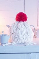 A handmade knitted tea cosy with a pompom