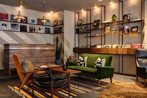Fifties-style, retro seating area with coffee table on brightly striped rug and books and records on illuminated modular shelving