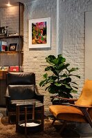 Retro armchairs at round side table and potted plant against white brick wall